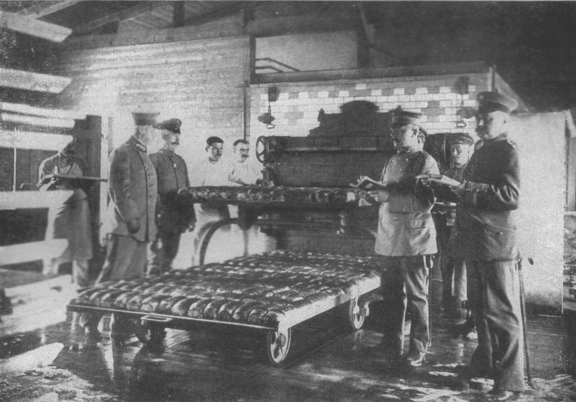A gauche : le commandant, examine le pain; devant, à droite:  le directeur responsable;  dans l'arrière-plan: boulangers français.