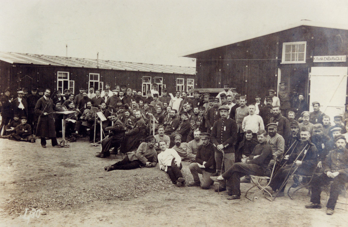 L'orchestre (à gauche) davant les baraques du Lazaret